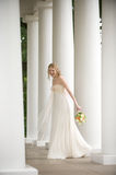 Smiling bride surrounded by columns Stock Photos