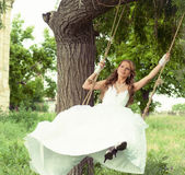 Smiling bride on the swings Stock Photography