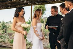 Beautiful wedding ceremony outdoors. Smiling bride talking with priest after the wedding ceremony under wedding arch. Beautiful wedding ceremony outdoors Royalty Free Stock Photography