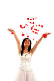 Smiling bride throws rose petals. Isolated over white background stock photos
