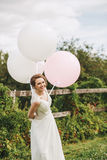 Smiling bride with two white balloons and one pink balloon Royalty Free Stock Photos