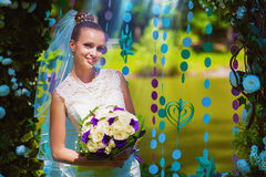 Smiling bride under flower arch Stock Images
