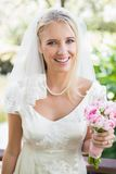 Smiling bride in a veil holding her bouquet looking at camera Royalty Free Stock Photography