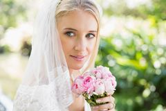 Smiling bride wearing veil holding bouquet. In the countryside Royalty Free Stock Photos