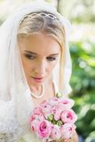 Smiling bride wearing veil holding bouquet looking down. In the countryside Stock Photo