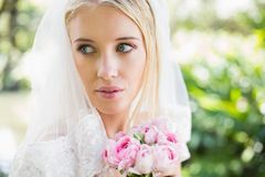 Smiling bride wearing veil holding bouquet looking over her shoulder. In the countryside Stock Photos