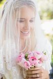 Smiling bride wearing veil over face holding bouquet. In the countryside Royalty Free Stock Photography