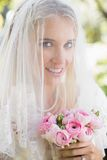 Smiling bride wearing veil over face holding bouquet looking at camera. In the countryside Royalty Free Stock Photography
