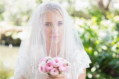 Smiling bride wearing veil over face holding rose bouquet. In the countryside Stock Photo