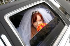 Smiling bride in wedding car limo. Portrait of smiling bride holding bouquer in wedding car limousine royalty free stock photos