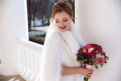 A smiling bride in a white fur cloak is walking along the bright hall. Portrait of a young girl who is getting married Royalty Free Stock Photo