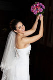Smiling bride in white wedding dress is throwing a. Beautiful bride with adorable smile is throwing her wedding bouquet of roses. White wedding dress. Dark stock photos