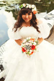Smiling bride in wreath with bouquet near lake Stock Image