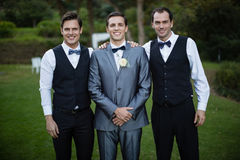Smiling bridegroom and best man standing in garden. Portrait of smiling bridegroom and best men standing in garden stock photo