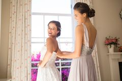Bridesmaid adjusting bride wedding dress in fitting room Stock Photography