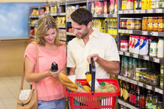 Smiling bright couple buying food porducts with shopping basket Stock Photos