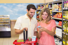 Smiling bright couple buying food products with shopping basket. At supermarket Royalty Free Stock Photos