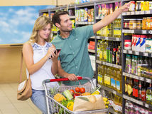 Smiling bright couple buying food products showing shelf Stock Photo