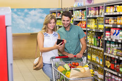 Smiling bright couple buying food products and using notebook Stock Photos