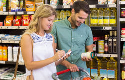 Smiling bright couple buying food products and writing on notebook Royalty Free Stock Photos