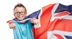 Smiling British superhero. Smiling British super hero wearing a flag as a cape and flying with raised fists Stock Images