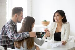 Smiling broker giving keys from first house to millennial couple royalty free stock photography