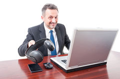 Smiling broker giving you his headphones Royalty Free Stock Photos