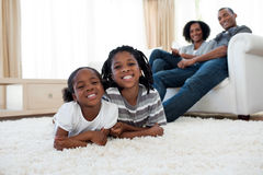 Smiling brother and sister lying on the floor Royalty Free Stock Image