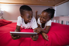 Smiling brother and sister using digital tablet while lying on bed Royalty Free Stock Images