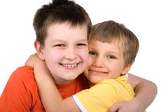 Smiling brothers hugging. Two cute, smiling brothers hugging each other over a white background royalty free stock image