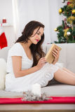 Smiling brown hair reading on the couch at christmas Royalty Free Stock Photography