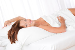 Smiling  brown hair woman lying in white bed Stock Photos