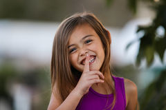 Smiling brown haired girl using finger to shush. Pretty four year old girl with brown hair has a big smile. Her head is tilted to one side. She is wearing a stock photo