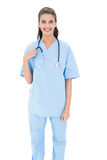 Smiling brown haired nurse in blue scrubs looking at camera Royalty Free Stock Photos