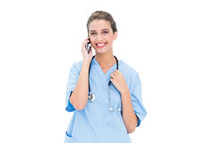 Smiling brown haired nurse in blue scrubs making a phone call Royalty Free Stock Photography