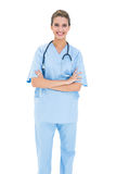 Smiling brown haired nurse in blue scrubs posing with arms crossed Stock Photos
