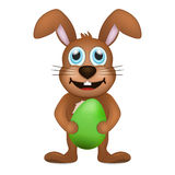 Smiling brown rabbit holds green easter egg Stock Photo