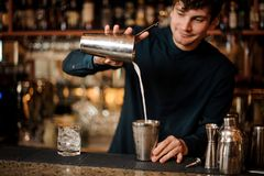 Smiling brunett bartender pouring an alcoholic cocktail into a steel shaker. Smiling brunet bartender pouring an alcoholic drink from the steel shaker on the bar royalty free stock photography