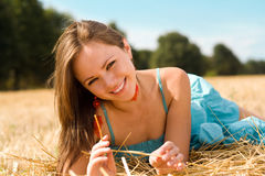Smiling brunette. Portrait of beautiful smiling brunette in the field royalty free stock photography