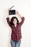 Smiling brunette actress with movie clapper board up Royalty Free Stock Photos
