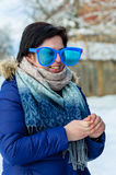 Smiling brunette adult girl in big clown glasses and blue jacket with scarf standing in turn of three-quarters. Portrait smiling brunette adult girl in big clown Stock Photo