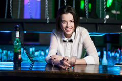 Smiling brunette bartender at nightclub. Orel, Russia - March 28TH, 2015: Beautiful smiling brunette bartender girl serves martini at nightclub 5 star Royalty Free Stock Images