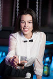 Smiling brunette bartender offering drink Royalty Free Stock Photos