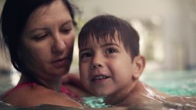 Smiling, brunette boy is swimming in the pool together with his mother. She is holding him and teaching how to swim. Family spending time together. Shooting stock footage
