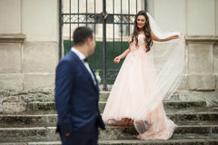 Smiling brunette bride walking down old stairs to handsome groom Royalty Free Stock Images