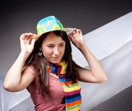 Smiling brunette in bright hat and colorful striped scarf Stock Images