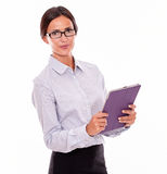 Smiling brunette businesswoman carrying a tablet Stock Photo