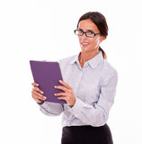 Smiling brunette businesswoman carrying a tablet Royalty Free Stock Photography