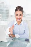 Smiling brunette businesswoman extending arm Royalty Free Stock Photography
