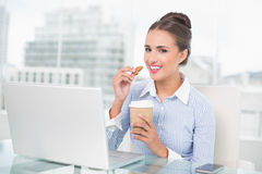 Smiling brunette businesswoman holding cookie Stock Image